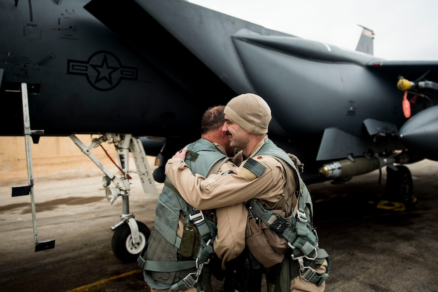 U. S. Air Force Col. David Brynteson, 332nd Expeditionary Operations Group commander, embraces his crewmate, after his fini flight, Jan. 27, 2016, in Southwest Asia. Brynteson has been commanding here for four months leading combat operations in the area of responsibility. (U.S. Air Force photo by Staff Sgt. Eboni Reams)