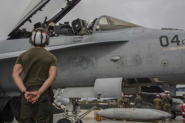 A U.S. Marine and pilots with Marine All Weather Fighter Attack Squadron (VMFA) 225 finish their final inspection of an F/A-18D Hornet before it takes off during exercise Cope North at Andersen Air Force Base, Guam, Feb. 3, 2017. Marines trained with the Royal Australian Air Force and Japan Air Self-Defense Force supporting theater security, focusing on dissimilar air combat training and large force employment. (U.S. Marine Corps photo by Cpl. Nathan Wicks)