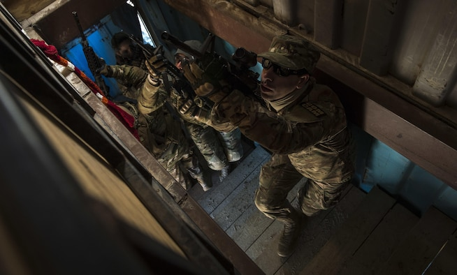 Combat camera Airmen clear a stairwell during close-quarters battle training at McCrady Training Center, Eastover, S.C., Jan. 27, 2017. Exercise Scorpion Lens is an annual 'ability to survive and operate' training exercise mandated by Air Force Combat Camera job qualification standards. The exercise's purpose is to provide refresher training to combat camera personnel in the areas of combat tactics, photography, videography and on procedures inherent to support combat camera mission tasks. (U.S. Air Force photo/Airman 1st Class James R. Crow)