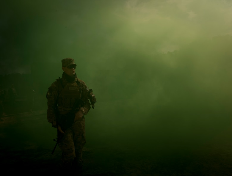 U. S. Air Force Staff Sgt. Nicholas Priest, 1st Combat Camera Squadron combat broadcast journalist, uses a smoke grenade as coverage for crossing an intersection during close quarters battle training at McCrady Training Center, Eastover, S. C., Jan. 27, 2017. Exercise Scorpion Lens is an annual Ability To Survive and Operate training exercise mandated by Air Force Combat Camera job qualification standards. Held at the United States Army Training Center Fort Jackson, S. C., and the McCrady Training Center, Eastover, S.C. the exercise's purpose is to provide refresher training to combat camera personnel. Individuals are instructed in the areas of combat tactics, photography, videography and on procedures inherent to support combat camera mission tasks. (U.S. Air Force photo by Airman 1st Class James R. Crow)