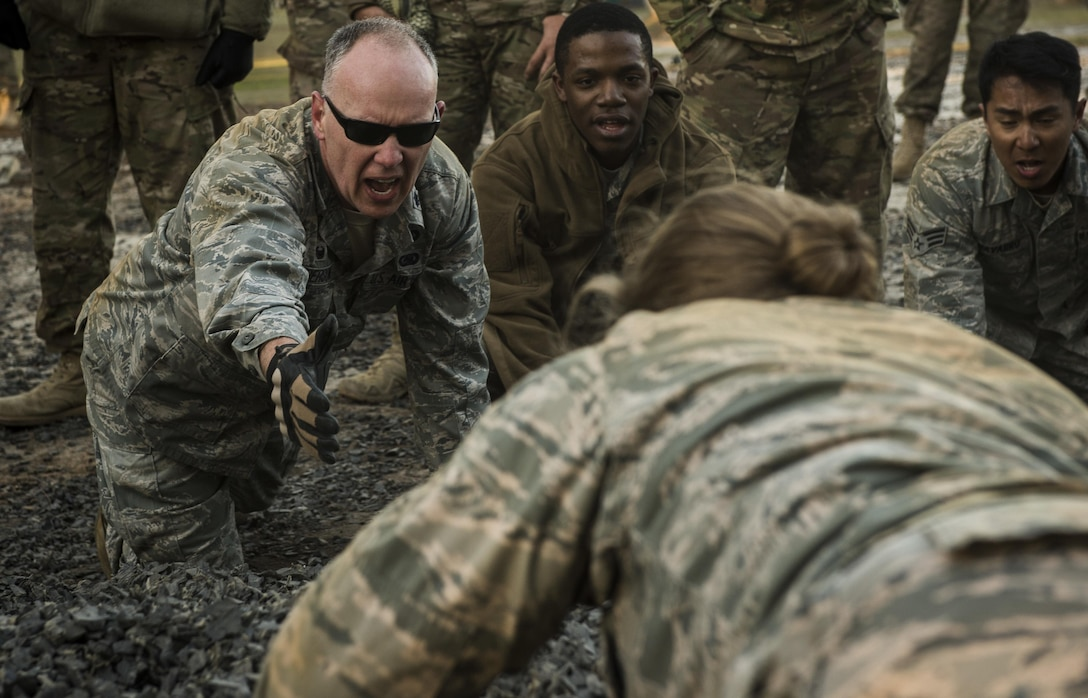 Lt. Col. Christopher Anderson, the 1st Combat Camera Squadron commander, reaches to assist a combat camera Airman during an obstacle course atthe U.S. Army Training Center in Fort Jackson, S.C., Jan. 29, 2017. Exercise Scorpion Lens is an annual 'ability to survive and operate' training exercise mandated by Air Force Combat Camera job qualification standards. The exercise's purpose is to provide refresher training to combat camera personnel in the areas of combat tactics, photography, videography and on procedures inherent to support combat camera mission tasks. (U.S. Air Force photo/Airman 1st Class James R. Crow)