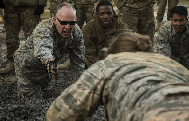 Lt. Col. Christopher Anderson, the 1st Combat Camera Squadron commander, reaches to assist a combat camera Airman during an obstacle course at the U.S. Army Training Center in Fort Jackson, S.C., Jan. 29, 2017. Exercise Scorpion Lens is an annual 'ability to survive and operate' training exercise mandated by Air Force Combat Camera job qualification standards. The exercise's purpose is to provide refresher training to combat camera personnel in the areas of combat tactics, photography, videography and on procedures inherent to support combat camera mission tasks. (U.S. Air Force photo/Airman 1st Class James R. Crow)