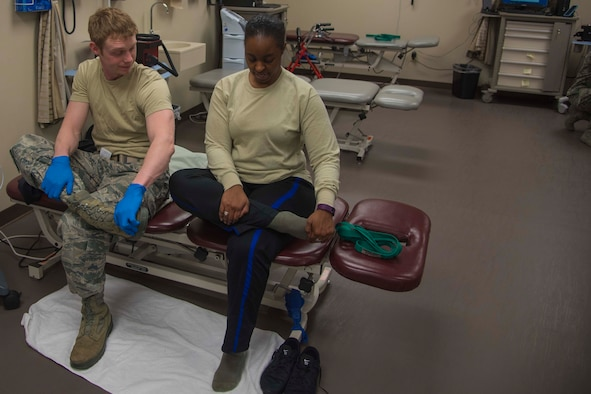 Staff Sgt. Kivynn Pabst, left, 779th Medical Group physical medicine technician, performs a stretch with Master Sgt. Christina Chislom, right, Malcolm Grow Medical Center patient, during a physical therapy appointment at Joint Base Andrews, Md., Feb. 2, 2017. Pabst gives Chislom treatment based on her unique needs.  (U.S. Air Force photo by Airman 1st Class Valentina Lopez)