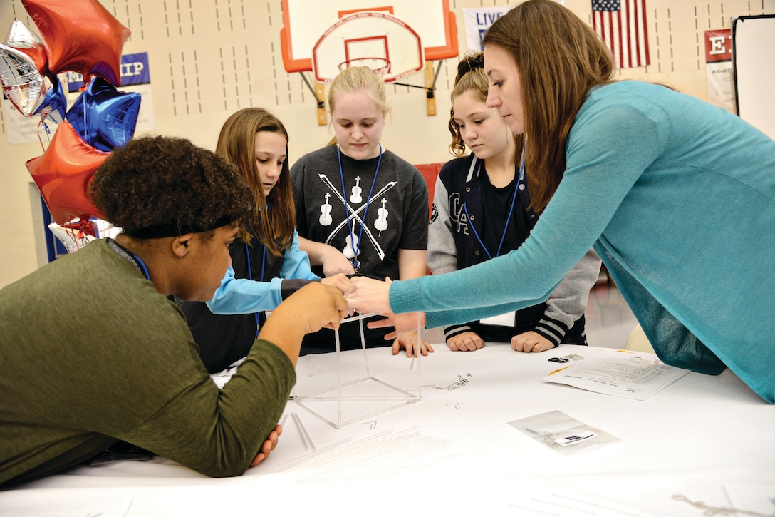 """Mentor Kerri Yap helps her team construct a tower made of straws as part of team building exercises at the first STEM Girls Camp, """"STEM Like a Girl"""". (Air Force photo by Kelly White)"""