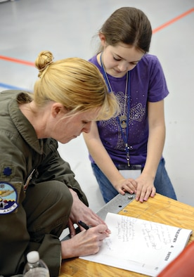 """Lt. Col. Kristen Thompson, Commander, 960th Airborne Air Control Squadron, signs an autograph for a student attending Tinker's first ever STEM Girls Camp, """"STEM Like a Girl"""" Jan. 28. (Air Force photo by Kelly White)"""