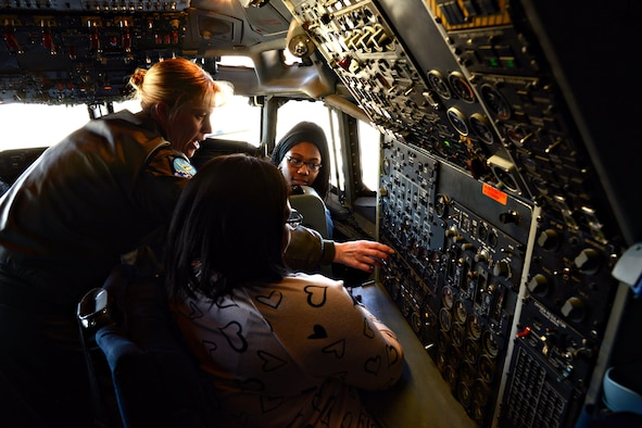 """Lt. Col. Kristen Thompson, Commander, 960th Airborne Air Control Squadron, explains some of the gauges on the flight deck of an E-3 Sentry aircraft to two girls attending the first STEM Girls Camp, """"STEM Like a Girl"""" held at Tinker, Jan. 28. (Air Force photo by Kelly White)"""
