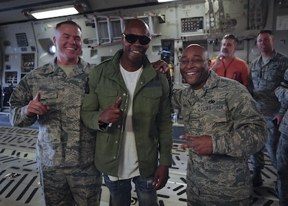 (from left)  Master Sgt. Mathew Hayes, 315th Aircraft Maintenance Squadron, Actor/comedian Dave Chappelle, and Tech Sgt. Philip Berry, 38th Aerial Port Squadron pose for a photo on a Joint Base Charleston, S.C. Feb. 2. Chappelle was in town for his stand-up comedy show when he made the visit to see service members and federal civilians at the base Feb. 2. (U.S. Air Force photo by Senior Airman Tom Brading)