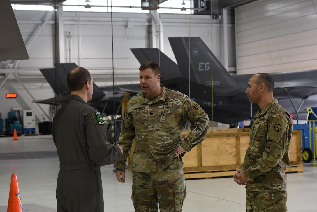 U.S. Air Force Lt. Col. Scott Gunn, 33rd Operations Support Squadron commander, left, discusses the weapons bay of an F-35A Lightning II with COL Samuel Saine, 4th Battlefield Coordination Detachment commander, center, and Sgt. Maj. Miguel Quiros, 4 BCD sergeant major, right, Jan. 26, 2017, at Eglin Air Force Base, Florida. Saine and Qurios visited the 33rd Fighter Wing while conducting a battlefield circulation analysis to engage with and evaluate Ground Liaison Officers embedded in the unit. (U.S. Air Force photo by Staff Sgt. Peter Thompson)