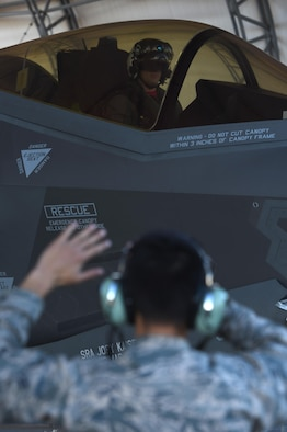 U.S. Air Force Airman 1st Class Jesse Wood, 33rd Aircraft Maintenance Squadron F-35A crew chief, marshals U.S. Navy Lt. Cmdr. Charles Escher, Strike Fighter Squadron (VFA-101) operations officer, Dec. 6, 2016, at Eglin Air Force Base, Florida. For only the second time at Eglin AFB, a Naval Aviator has been selected to dual qualify in the U.S. Navy's F-35C and the Air Force's F-35A. Escher plans to use what he learns from his experience with the 33 FW to help the F-35 enterprise grow. He looks to join a group of test pilots at Edwards AFB, California, where he will have the opportunity to be the Navy's voice for the aircraft weapons and vehicle system development. (U.S. Air Force photo/ Staff Sgt. Peter Thompson)