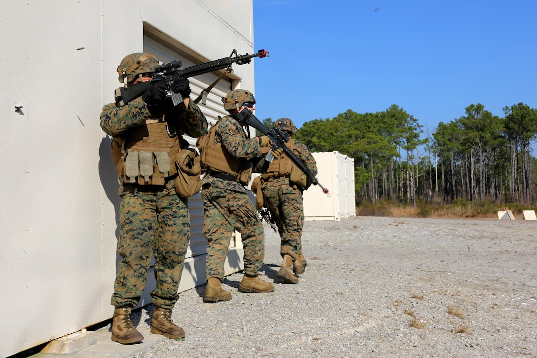 Marines provide security while maneuvering around a building during Military Operations in Urban Terrain training aboard Marine Corps Outlying Field Atlantic, N.C., Feb. 2, 2017. Nearly 40 Marines with supporting personnel participated in the weeklong training that simulated hostile takeovers and how to overcome unexpected situations with small unit leadership. The Marines are assigned to Marine Wing Support Squadron 271, Marine Aircraft Group 14, 2nd Marine Aircraft Wing. (U.S. Marine Corps photo by Cpl. Jason Jimenez/ Released)