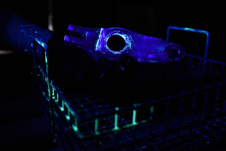 U.S. Air Force Airman 1st Class James Schwein, 19th Maintenance Squadron nondestructive inspections journeyman, uses a black light to inspect an aircraft tow fitting arm for cracks Jan. 19, 2017, at Little Rock Air Force Base, Ark. Liquid penetrant fills in small cracks causing them to become fluorescent under black lighting, making it easier to detect cracks and corrosion. (U.S. Air Force photo by Airman 1st Class Kevin Sommer Giron)