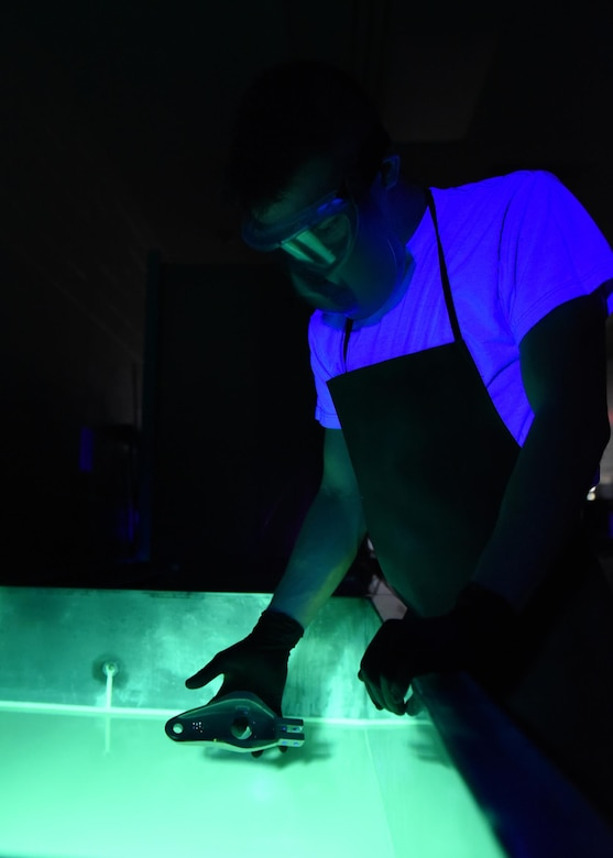 U.S. Air Force Airman 1st Class James Schwein, 19th Maintenance Squadron nondestructive inspections journeyman, submerges a C-130J tow fitting arm into liquid fluorescent penetrant Jan. 31, 2017, at Little Rock Air Force Base, Ark. The penetrant seeps into tiny openings in the part to identify potential cracks. (U.S. Air Force photo by Airman 1st Class Kevin Sommer Giron)