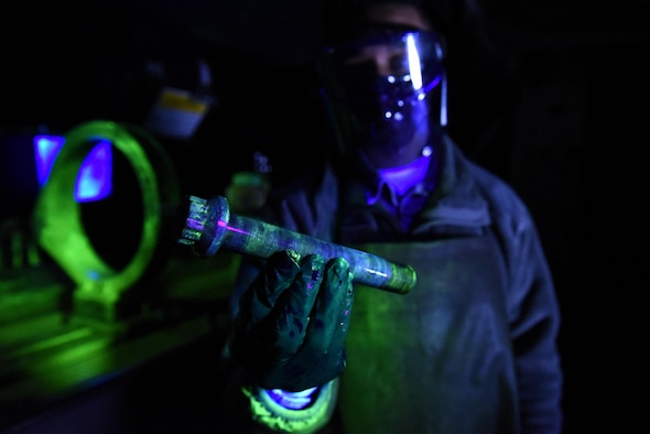 U.S. Air Force Airman 1st Class Brandon Davis, 19th Maintenance Squadron nondestructive inspections journeyman, holds an inspected main landing wheel bolt at Little Rock Air Force Base, Ark. NDI Airmen find small cracks in aircraft parts by running them through multiple chemical baths and using black lights to illuminate the defects. (U.S. Air Force photo by Airman 1st Class Kevin Sommer Giron)