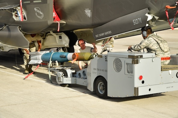An Air Force weapons load crew assigned to the 34th Aircraft Maintenance Unit, Hill Air Froce Base, Utah, loads a GBU-12 into an F-35A Lightning II aircraft at Nellis AFB, Nevada, Feb. 1, 2017. (U.S. Air Force photo/R. Nial Bradshaw)