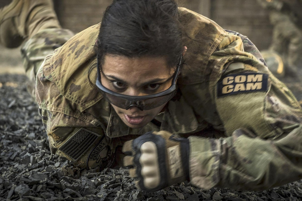 An airman low crawls while navigating an obstacle course.