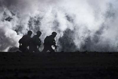 Three Marines, shown in silhouette, run as smoke billows behind them.