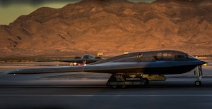 Two B-2 Sprit stealth bombers assigned to the 509th Bomb Wing, Whiteman Air Force Base, Missouri, taxi down the runway as they prepare to takeoff during Deliberate Strike Night at Nellis Air Force Base, Nevada, June 16, 2016. Two B-2s departed Whiteman Air Force Base, Missouri for a transatlantic flight to Libya on Jan. 18 in what would become the B-2's first combat mission since Operation Odyssey Dawn in 2011. (U.S. Air Force photo by Airman 1st Class Kevin Tanenbaum)