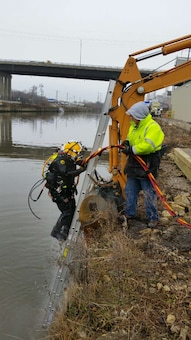 Dive Supervisor Shanon Chader assists Diver Steve England to exit the water.