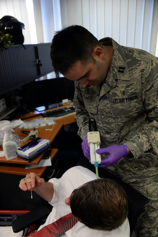 Capt. Christopher Tracy, 86th Dental Squadron dentist, applies molding material to the ear of an Air Force Office of Special Investigations agent at an OSI office at Ramstein Air Base, Germany, Jan. 6, 2017. Each mold took 10 to 15 minutes to become firm enough to remove. (U.S. Air Force photo by Airman 1st Class D. Blake Browning)