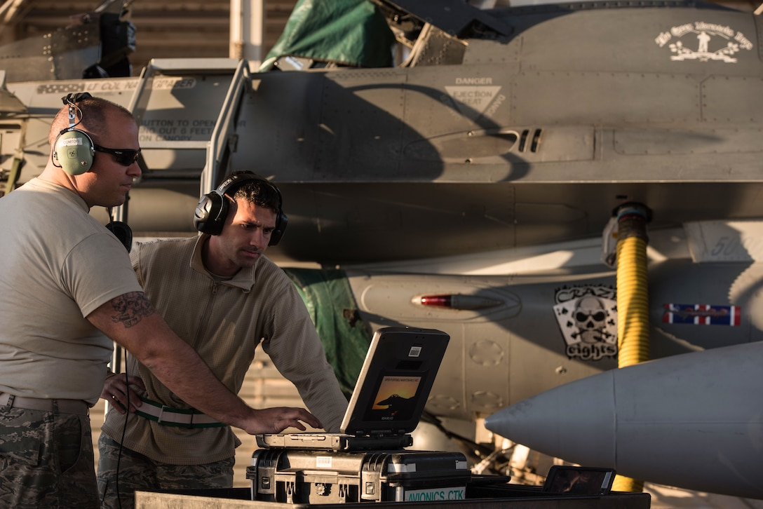 Tech. Sgt. Alex Babbie and Senior Airmen Josh Clemons, 407th Expeditionary Maintenance Squadron avionics specialists, reprogram the common central interface unit of an F-16 Fighting Falcon at the 407th Air Expeditionary Group Feb. 4, 2017. The CCIU acts as the weapons brain for the aircraft and must be programmed for the combat load the aircraft is carrying.  (U.S. Air Force photo/Master Sgt. Benjamin Wilson)(Released)