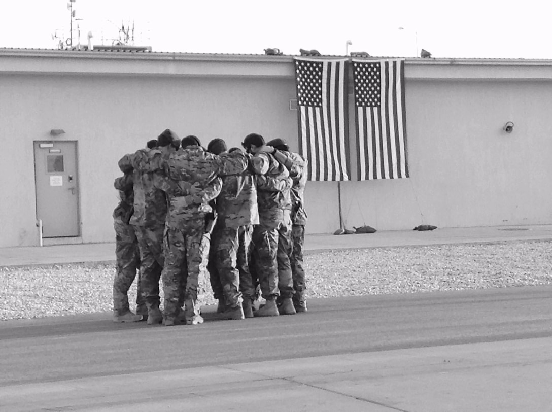 Soldiers of Special Forces Operational Detachment - Alpha 0224, 10th Special Forces Group (Airborne) huddle together for strength as they memorialize two of their fallen brothers during a memorial held at Kunduz Airfield in Afghanistan on Nov. 7, 2016. Maj. Andrew Byers, the commander for ODA 0224, and Sgt. 1st Class Ryan Gloyer, an intelligence sergeant with ODA 0224, were killed in action during the Battle of Boz Qandahari, Afghanistan, on Nov. 2-3, 2016. (Courtesy Photo)