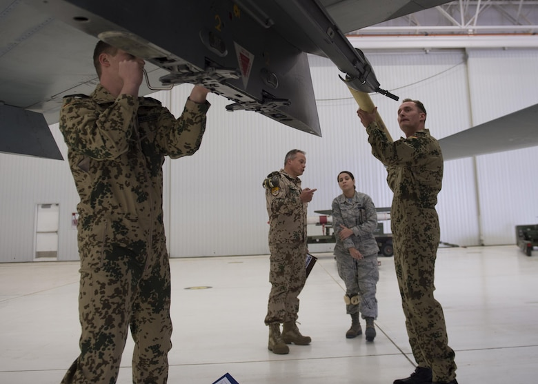 German Air Force Flying Training Center members load an inert missile onto a GAF Tornado during a quarterly load crew competition at Holloman Air Force Base, N.M., Jan. 20, 2016. The GAF competed for the last time in the load crew competition to have their skills evaluated alongside the MQ-9 Reaper, and the F-16 Fighting Falcon load crews. Points for the competition are awarded based on weapons loading, tool kit inspection and uniform inspection categories. (U.S. Air Force photo by Senior Airman Chase Cannon/ Released)