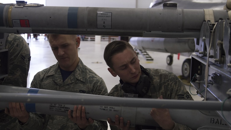 Members of the 54th Fighter Group load crew prepare to load an inert munition onto an F-16 Fighting Falcon during a quarterly load crew competition at Holloman Air Force Base, N.M., Jan. 20, 2016. The weapons load crews for German Air Force Tornado, F-16 Fighting Falcon and MQ-9 Reaper competed against each other to load weapons the most efficiently and with the least amount of procedural errors. Points for the competition are awarded based on weapons loading, tool kit inspection and uniform inspection categories. (U.S. Air Force photo by Senior Airman Chase Cannon/ Released)