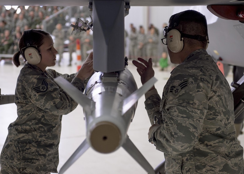 Members of the 49th Wing Maintenance Group inspect an inert munition before loading it onto an MQ-9 Reaper during a quarterly load crew competition at Holloman Air Force Base, N.M., Jan. 20, 2016. The weapons load crews for German Air Force Tornado, F-16 Fighting Falcon and MQ-9 Reaper competed against each other to load weapons the most efficiently and with the least amount of procedural errors. Points for the competition are awarded based on weapons loading, tool kit inspection and uniform inspection categories. (U.S. Air Force photo by Senior Airman Chase Cannon/ Released)