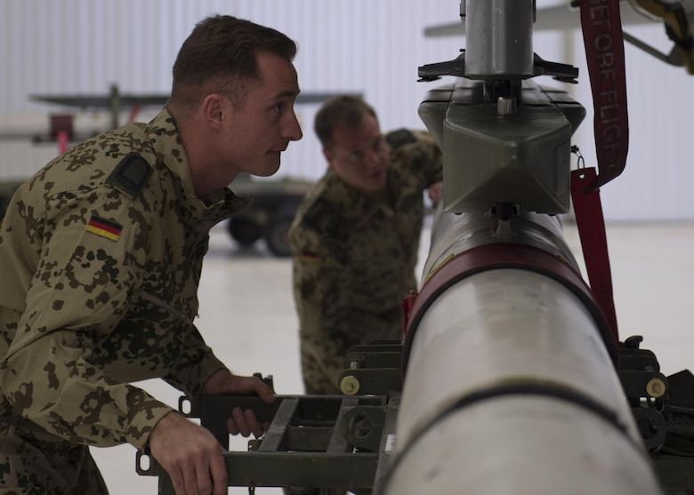 German Air Force Flying Training Center members load an inert munition onto a GAF Tornado during a quarterly load crew competition at Holloman Air Force Base, N.M., Jan. 20, 2016. The GAF competed for the last time in the load crew competition to have their skills evaluated alongside the MQ-9 Reaper, and the F-16 Fighting Falcon load crews. Points for the competition are awarded based on weapons loading, tool kit inspection and uniform inspection categories. (U.S. Air Force photo by Senior Airman Chase Cannon/ Released)