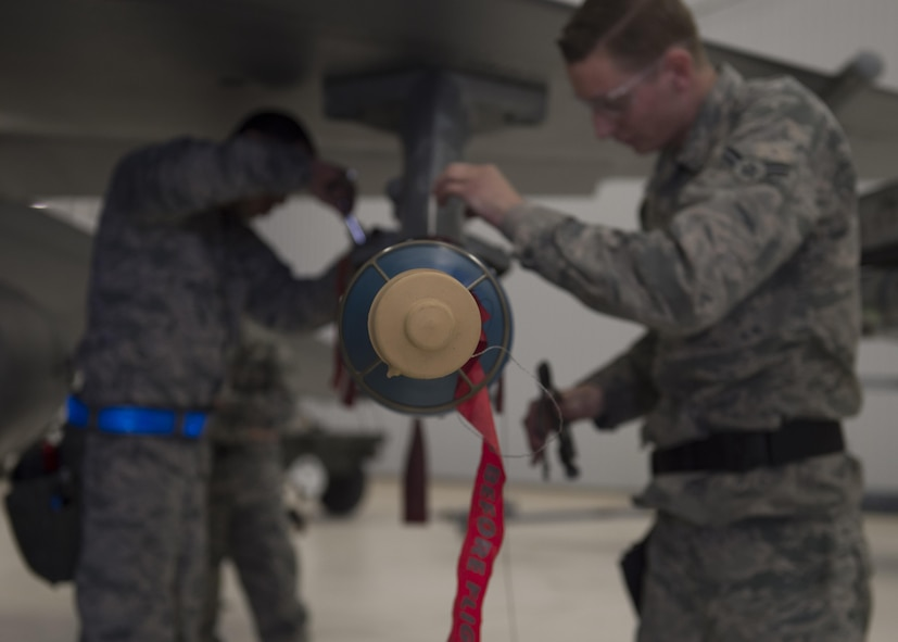 Members of the 54th Fighter Group load crew secure an inert munition onto an F-16 Fighting Falcon during a quarterly load crew competition at Holloman Air Force Base, N.M., Jan. 20, 2016. The weapons load crews for German Air Force Tornado, F-16 Fighting Falcon and MQ-9 Reaper competed against each other to load weapons the most efficiently and with the least amount of procedural errors. Points for the competition are awarded based on weapons loading, tool kit inspection and uniform inspection categories. (U.S. Air Force photo by Senior Airman Chase Cannon/ Released)