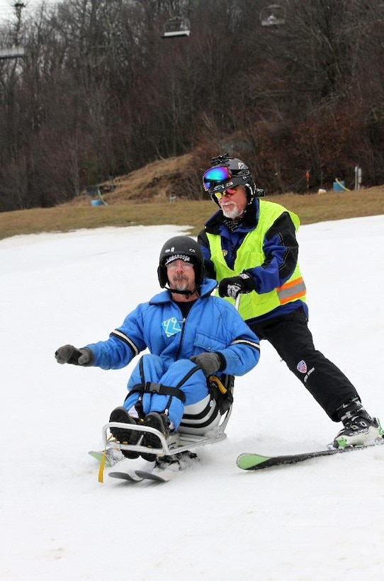 Marcus Brumbaugh, an electrical mechanic from the Nashville District skies downhill with military veteran Dean Tisdale an adaptive skier during the 36th Disabled Sports USA Adaptive Learn to Ski event clinic held Jan. 19, 2017 at the Beech Mountain Resort in Beech Mountain, N.C.