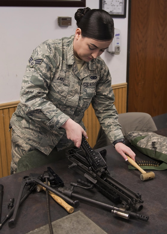 Senior Airman Bailey Lake, 5th Security Forces Squadron combat arms training and maintenance student, takes apart an M249 light machine gun at the CATM site on Minot Air Force Base, N.D., Feb. 1, 2017. To qualify on a firearm at CATM, every student must be able to break down and rebuild the firearm. (U.S. Air Force photo/Airman 1st Class Alyssa M. Akers)