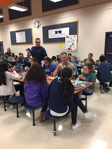 Marines help with the Lunch Buddy Program at Shirley Heim Middle School