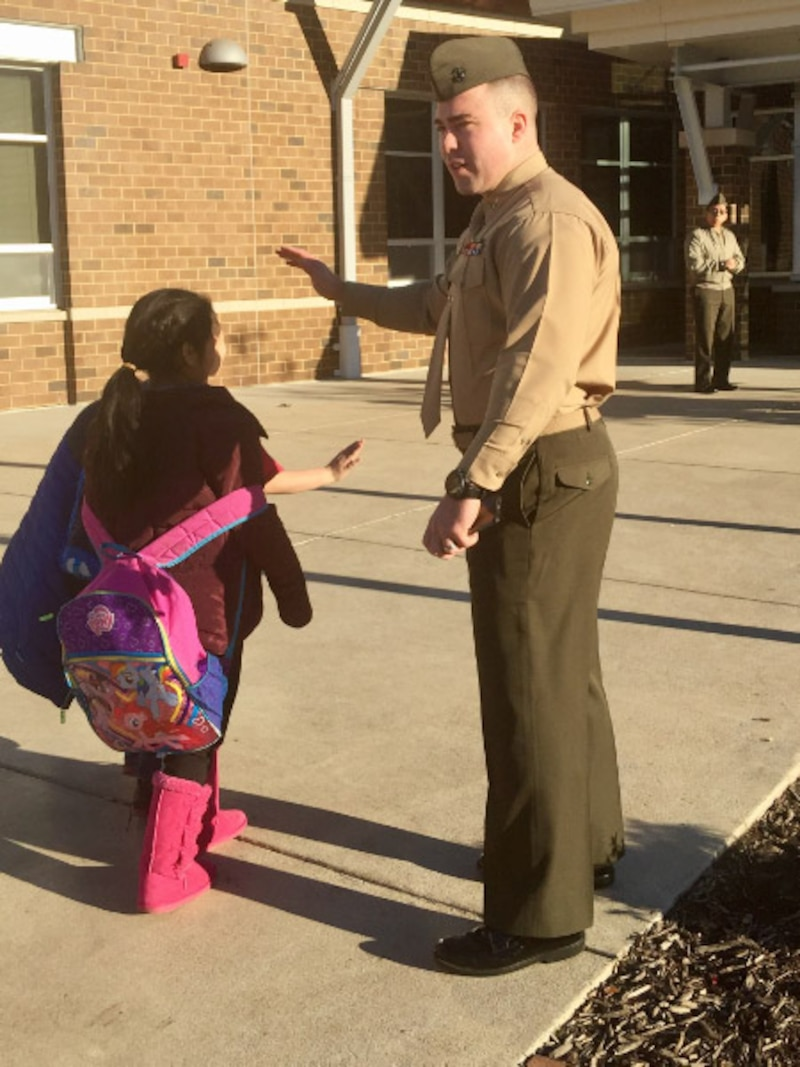 Capt Magyar welcoming students with a high five at Triangle Elementary School.