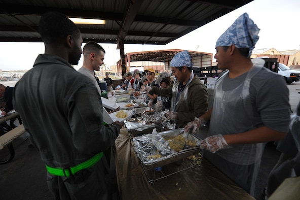 Volunteers from the 56th Fighter Wing Chaplain office serve free meals to Airmen and their families during the monthly flight line feast, Feb. 2, 2017 at Luke Air Force Base, Ariz. The flight line feast is one of many community outreach events the chaplain's office holds to get Airmen more involved and comfortable with the chaplains and the services they offer. (U.S. Air Force photo by Airman 1st Class Caleb Worpel)