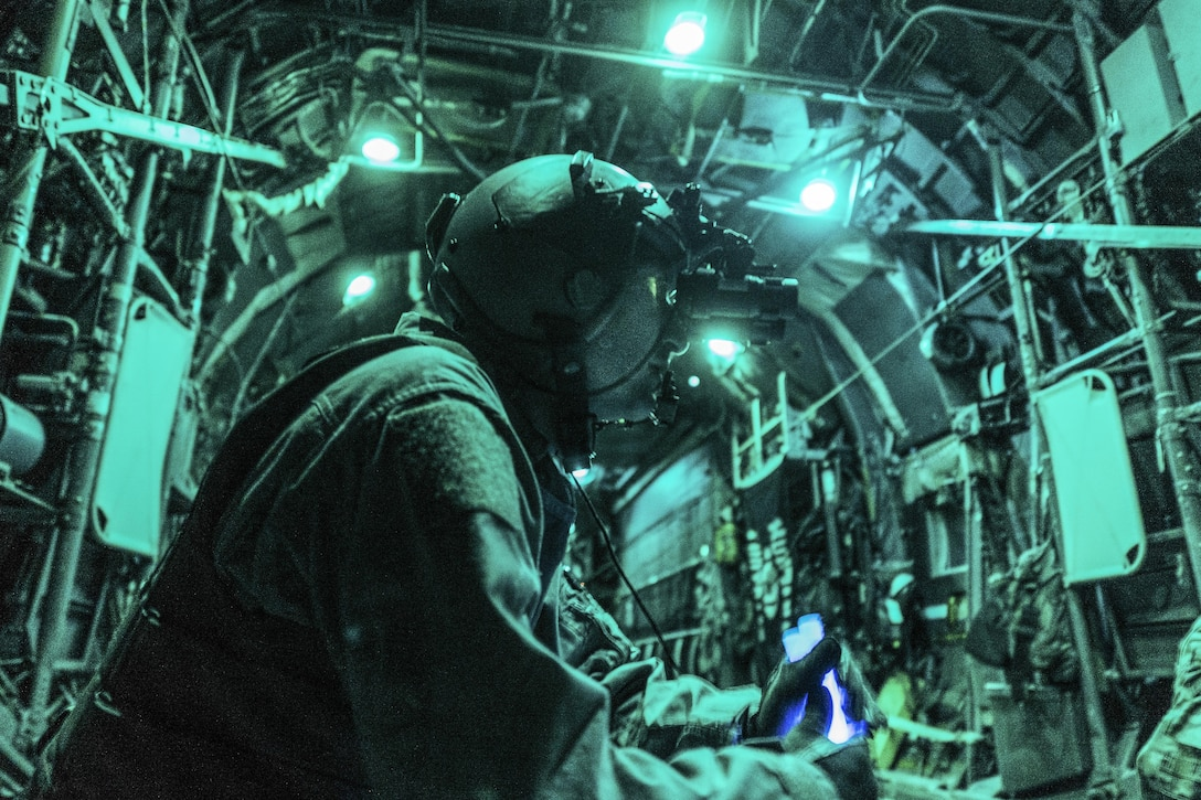 Air Force Tech. Sgt. Nathan Schultz waits to secure a load of cargo in a C-130H Hercules