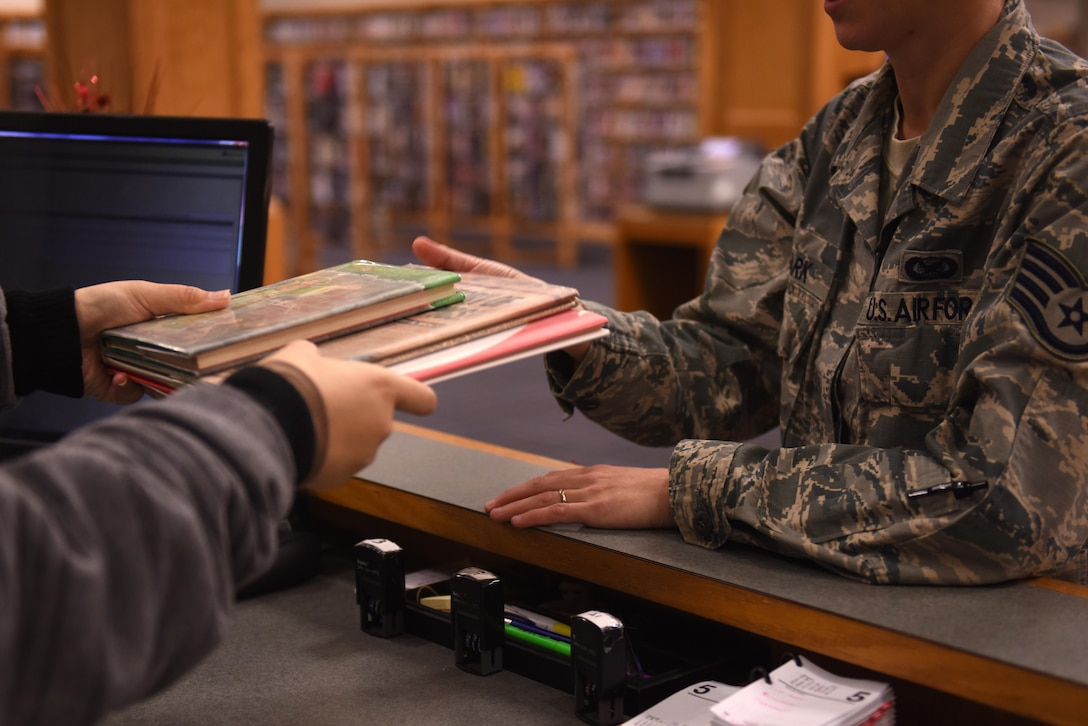 A military member checks out a book at the Little Rock Air Force Base Library Jan. 18, 2017. The LRAFB library, located in the Walters Community Center, has a growing collection of more than 20,000 books, 5,000 DVD's, 100 music CD's, 1,000 audio books, several different games for a variety of gaming systems, and 80 periodical and newspaper subscriptions. (U.S. Air Force photo by Airman 1st Class Codie Collins)