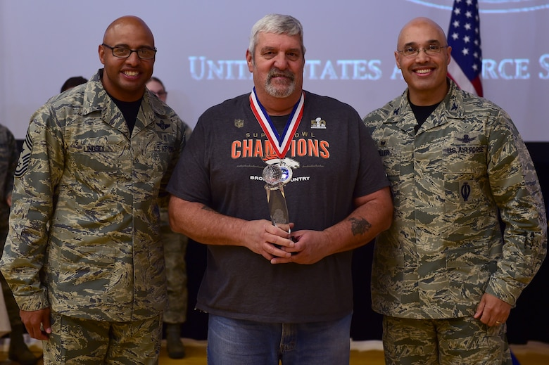 Ernie Gordon, 460th Mission Support Group, center, receives the Civilian Category I, Non-supervisory of the Year Award, from Col. David Miller Jr., 460th Space Wing commander, and Chief Master Sgt. Rod Lindsey, 460th SW command chief, Feb. 3, 2017, at the annual awards on Buckley Air Force Base, Colo. The annual awards is a ceremony that recognizes the significant achievements, dedication and skill of the military and civilian members of the 460th SW. (U.S. Air Force photo by Airman Jacob Deatherage/Released)