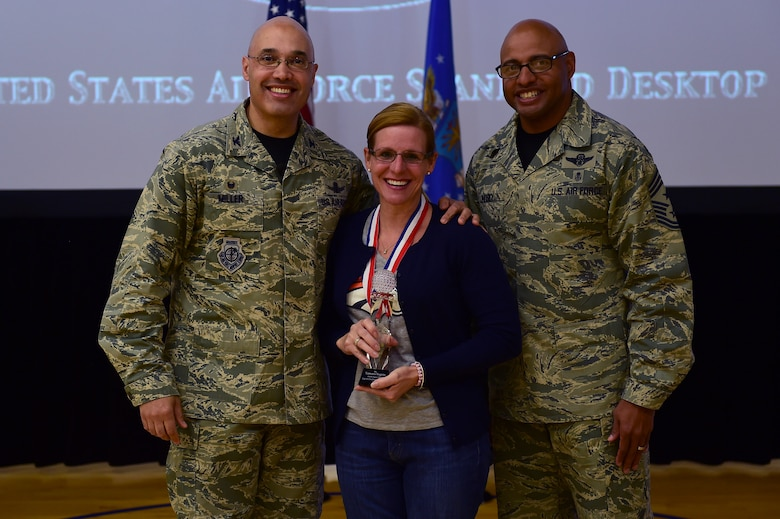 Tamura Vugrin, 460th Mission Support Group, center, receives the Civilian Category II, Non-supervisory of the Year Award, from Col. David Miller Jr., 460th Space Wing commander, and Chief Master Sgt. Rod Lindsey, 460th SW command chief, Feb. 3, 2017, at the annual awards on Buckley Air Force Base, Colo. The annual awards is a ceremony that recognizes the significant achievements, dedication and skill of the military and civilian members of the 460th SW. (U.S. Air Force photo by Airman Jacob Deatherage/Released)