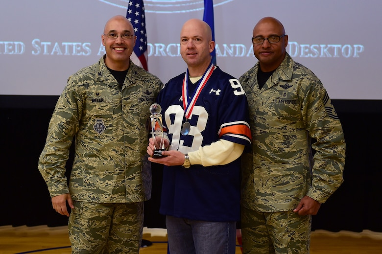 Mark Laudenslager, 460th Mission Support Group, center, receives the Civilian Category II Supervisory of the Year Award, from Col. David Miller Jr., 460th Space Wing commander, and Chief Master Sgt. Rod Lindsey, 460th SW command chief, Feb. 3, 2017, at the annual awards on Buckley Air Force Base, Colo. The annual awards is a ceremony that recognizes the significant achievements, dedication and skill of the military and civilian members of the 460th SW. (U.S. Air Force photo by Airman Jacob Deatherage/Released)