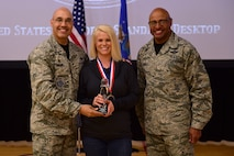 Autumn Hammer, Buckley key spouse, center, receives the Key Spouse of the Year Award, from Col. David Miller Jr., 460th Space Wing commander, and Chief Master Sgt. Rod Lindsey, 460th SW command chief, Feb. 3, 2017, at the annual awards on Buckley Air Force Base, Colo. The annual awards is a ceremony that recognizes the significant achievements, dedication and skill of the military and civilian members of the 460th SW. (U.S. Air Force photo by Airman Jacob Deatherage/Released)