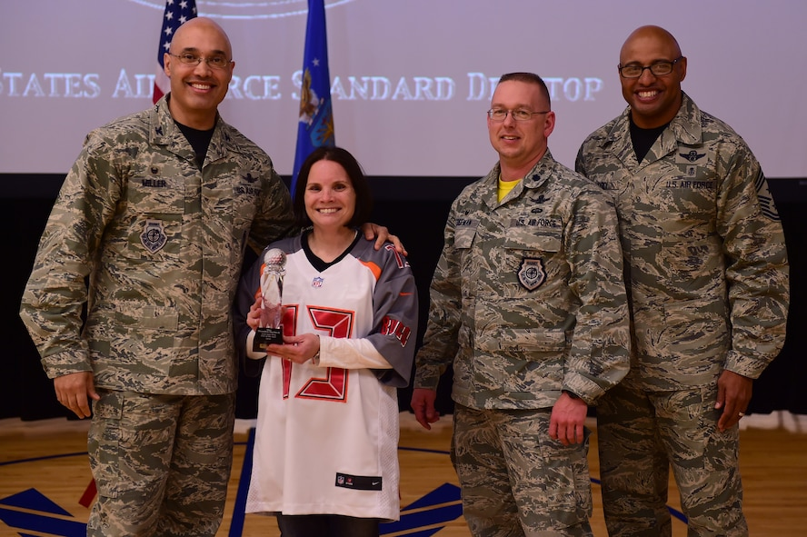 Lt. Col. April Wimmer, 2nd Space Warning Squadron commander, and Lt. Col. Paul Freeman, 460th Operations Support Squadron commander, center, accept the Field Grade Officer Award for Maj. Brendon Herbeck, 460th Operations Support Group, from Col. David Miller Jr., 460th Space Wing commander, and Chief Master Sgt. Rodney Lindsey, 460th SW command chief, Feb. 3, 2017, at the annual awards on Buckley Air Force Base, Colo. The annual awards is a ceremony that recognizes the significant achievements, dedication and skill of the military and civilian members of the 460th SW. (U.S. Air Force photo by Airman Jacob Deatherage/Released)