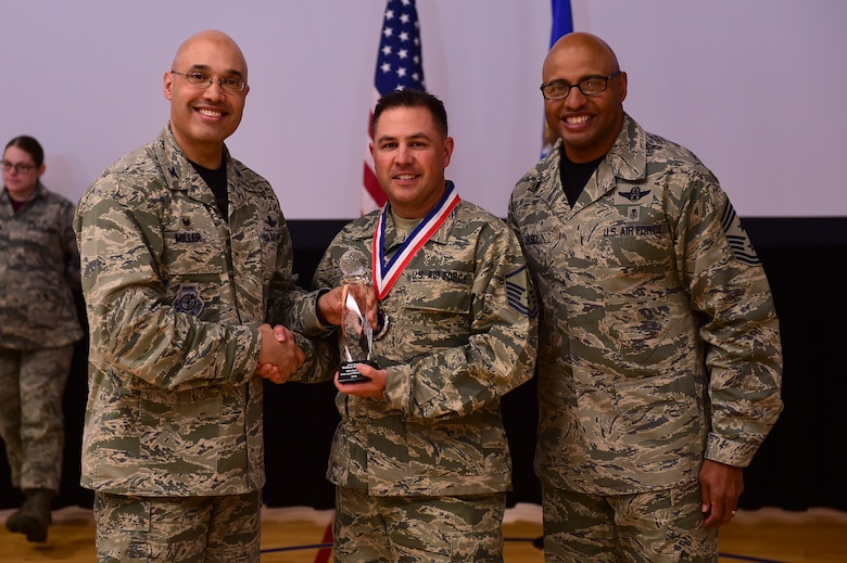 Master Sgt. Wolfram Stumpf, Mile High Honor Guard NCO, center, receives the Honor Guard NCO of the Year Award, from Col. David Miller Jr., 460th Space Wing commander, and Chief Master Sgt. Rod Lindsey, 460th SW command chief, Feb. 3, 2017, at the annual awards on Buckley Air Force Base, Colo. The annual awards is a ceremony that recognizes the significant achievements, dedication and skill of the military and civilian members of the 460th SW. (U.S. Air Force photo by Airman Jacob Deatherage/Released)