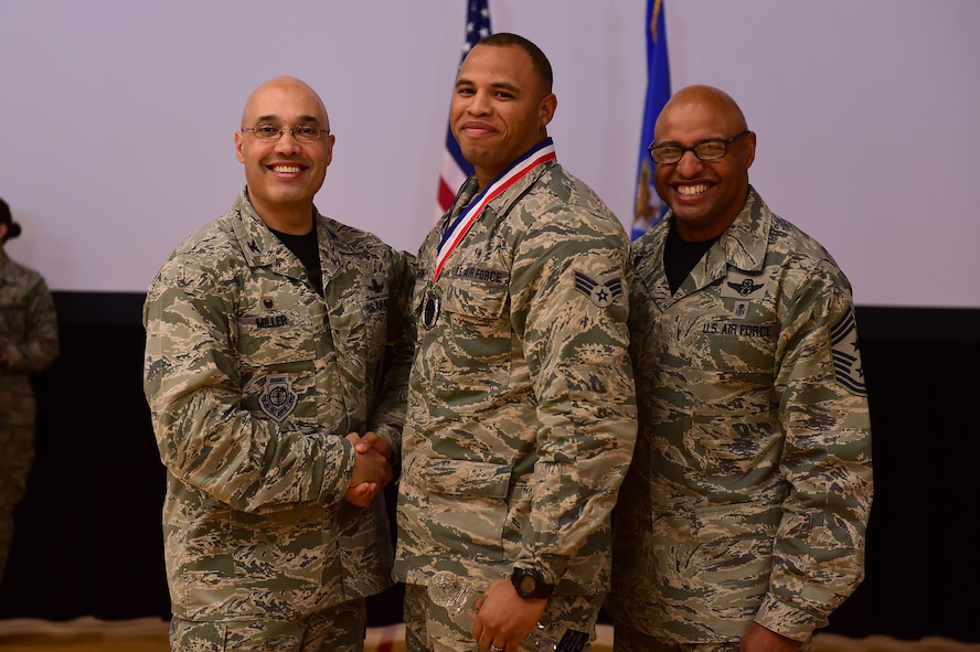 Senior Airman Matthew Thompson, Mile High Honor Guard Airman, center, receives the Honor Guard Airman of the Year Award, from Col. David Miller Jr., 460th Space Wing commander, and Chief Master Sgt. Rod Lindsey, 460th SW command chief, Feb. 3, 2017, at the annual awards on Buckley Air Force Base, Colo. The annual awards is a ceremony that recognizes the significant achievements, dedication and skill of the military and civilian members of the 460th SW. (U.S. Air Force photo by Airman Jacob Deatherage/Released)