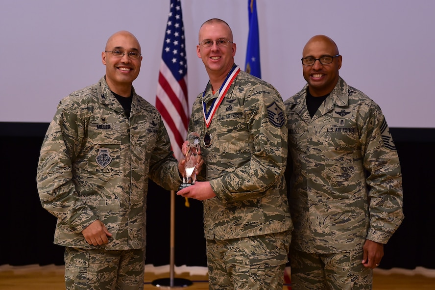 Master Sgt. Robert Hotzfeld, 460th Mission Support Group, center, receives the First Sergeant of the Year Award, from Col. David Miller Jr., 460th Space Wing commander, and Chief Master Sgt. Rod Lindsey, 460th SW command chief, Feb. 3, 2017, at the annual awards on Buckley Air Force Base, Colo. The annual awards is a ceremony that recognizes the significant achievements, dedication and skill of the military and civilian members of the 460th SW. (U.S. Air Force photo by Airman Jacob Deatherage/Released)