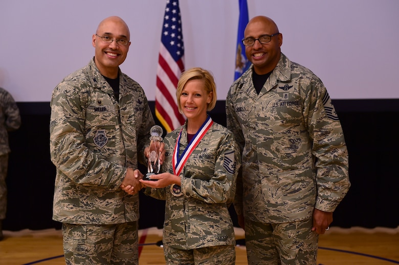Master Sgt. Stacey Lindsey, 460th Medical Group, receives the Senior NCO of the Year Award, from Col. David Miller Jr., 460th Space Wing commander, and Chief Master Sgt. Rod Lindsey, 460th SW command chief, Feb. 3, 2017, at the annual awards on Buckley Air Force Base, Colo. The annual awards is a ceremony that recognizes the significant achievements, dedication and skill of the military and civilian members of the 460th SW. (U.S. Air Force photo by Airman Jacob Deatherage/Released)