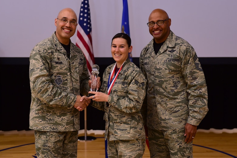 Senior Airman Sarah Gilbert, 460th Medical Group, receives the Airman of the Year Award, from Col. David Miller Jr., 460th Space Wing commander, and Chief Master Sgt. Rod Lindsey, 460th SW command chief, Feb. 3, 2017, at the annual awards on Buckley Air Force Base, Colo. The annual awards is a ceremony that recognizes the significant achievements, dedication and skill of the military and civilian members of the 460th SW. (U.S. Air Force photo by Airman Jacob Deatherage/Released)