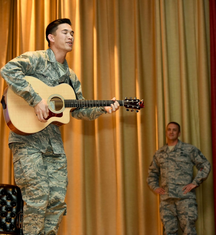 """Senior Airman James Pratt, a heavy equipment operator assigned to the 28th Civil Engineer Squadron, performs John Mayer's """"Age of Worry"""" in front of the 28th Mission Support Group inside the base theater during their annual awards ceremony, Jan. 26, 2017, at Ellsworth Air Force Base, S.D. Pratt applied for the Air Force Entertainer of the Year by submitting a cell-phone video of himself performing a song. On Jan. 30, he was announced as the recipient of the Air Force-wide award and coined by Col. Gentry Boswell, the commander of the 28th Bomb Wing.  (U.S. Air Force photo by Airman 1st Class Randahl J. Jenson)"""