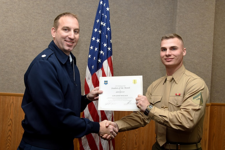 U.S. Air Force Lt. Col. Jason Kulchar, 315th Training Squadron director of operations, presents the 316th Training Squadron Student of the Month award for January 2017 to Lance Cpl. Jesse Wallace, 316th TRS student, in the Brandenburg Hall on Goodfellow Air Force Base, Texas, Feb. 3, 2017. (U.S. Air Force photo by Staff Sgt. Joshua Edwards/Released)