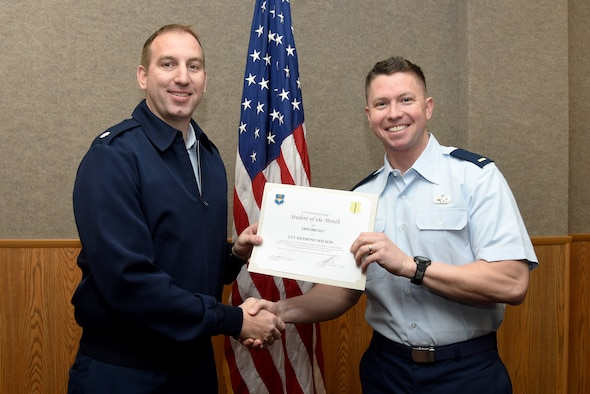 U.S. Air Force Lt. Col. Jason Kulchar, 315th Training Squadron director of operations, presents the 315th Officer Training Squadron Student of the Month award for January 2017 to 2nd Lt. Anthony Wilson, 315th TRS student, in the Brandenburg Hall on Goodfellow Air Force Base, Texas, Feb. 3, 2017. (U.S. Air Force photo by Staff Sgt. Joshua Edwards/Released)